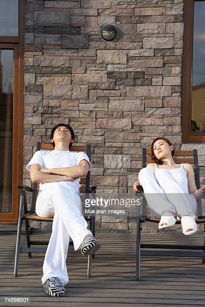 A young man and a young woman relax sunbathing on the patio (front view).