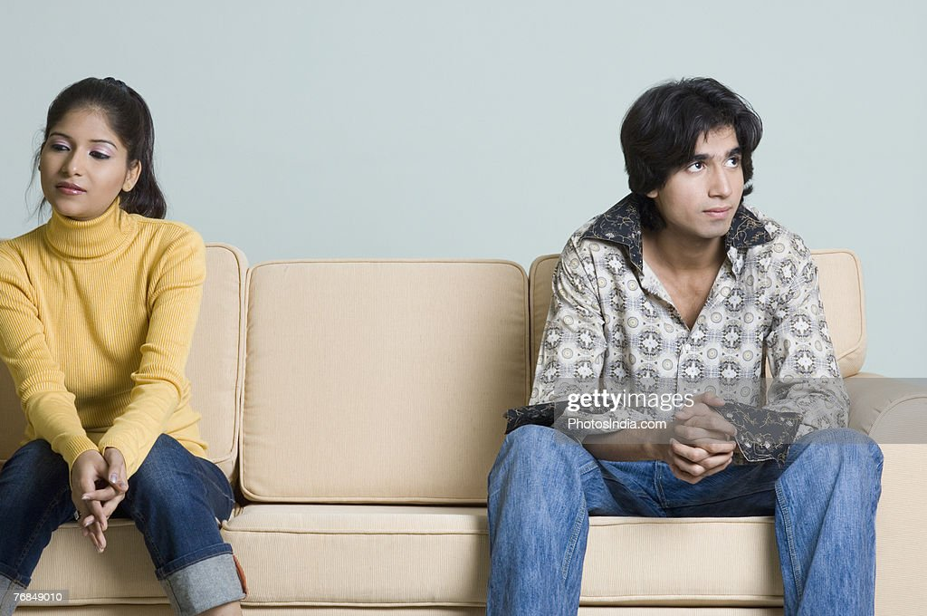 Young man and a young woman sitting on a couch : Stock Photo