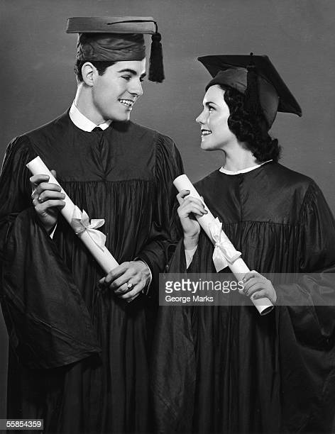 A young man and a young woman wear the cap and gown outfit that symbolizes the college graduate in North America mid 20th Century They also hold...