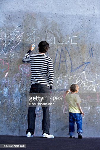 Young man and boy (2-4), drawing on wall with chalk, rear view : Stock Photo