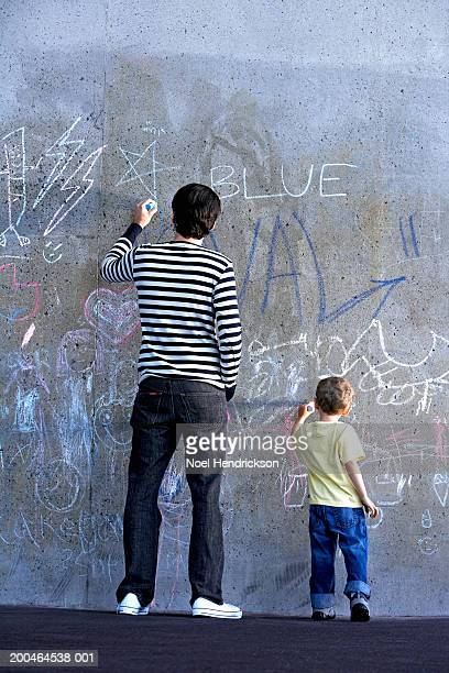 Young man and boy (2-4), drawing on wall with chalk, rear view