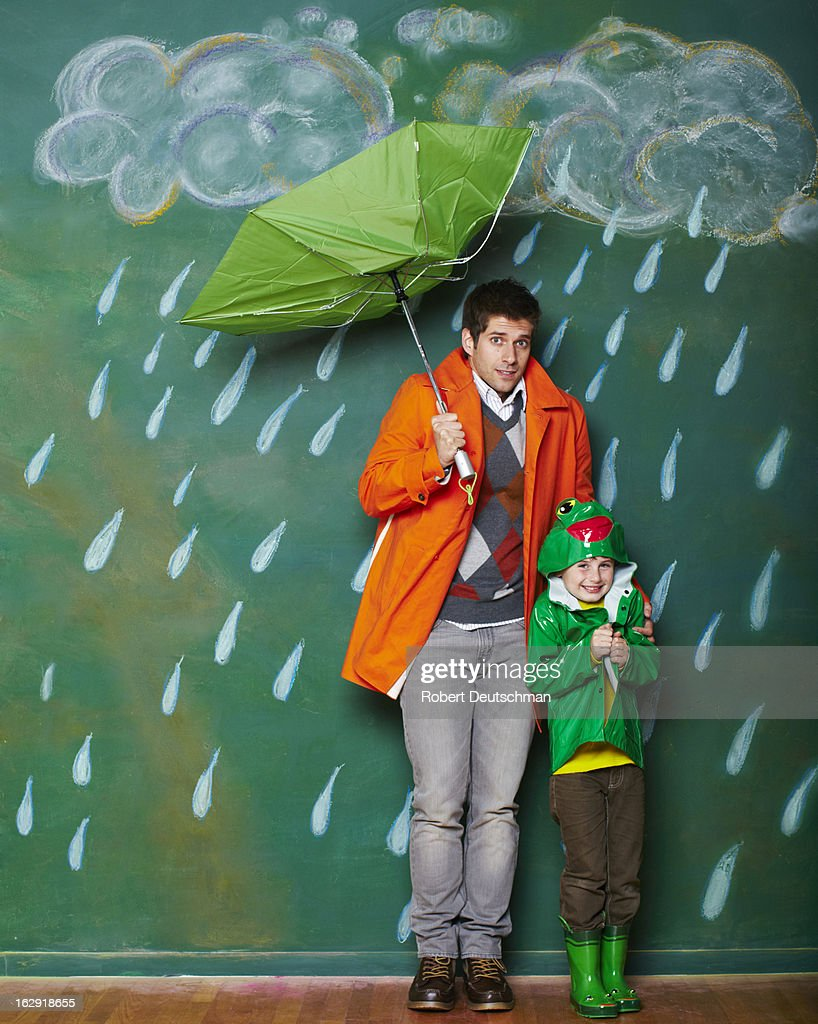 A young man and boy huddling from the rain. : Stock Photo