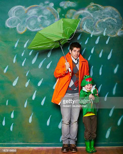 A young man and boy huddling from the rain.