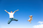 happy young man and dog jumping in the sky together