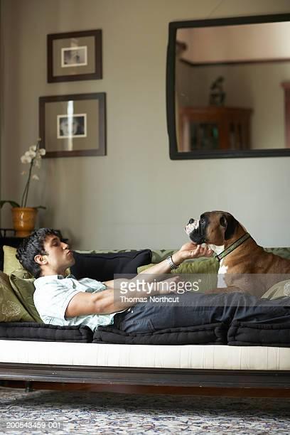 Junger Mann mit Hund auf dem sofa liegende, Mann streicheln Hund, Seitenansicht