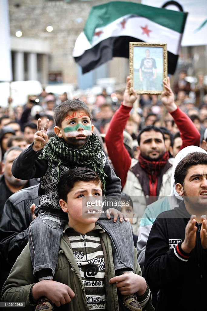 A young man and his baby brother gesture during an anti-Assad protest in the town of Binnish on April 9, 2012 in Syria. Conitnuing violence in northern Syria between government forces and rebels is putting plans for a UN-brokered Syria ceasefire on Tuesday in jeopardy.