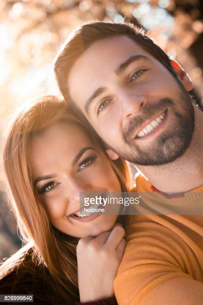 Young man and his girlfriend enjoying time spend together in public park, looking at camera.