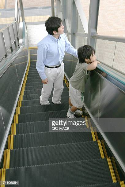 Young man and his son on an escalator