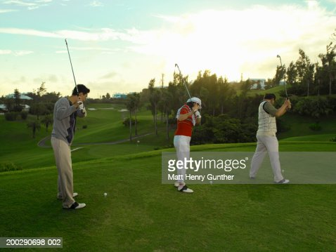 Young man and mature couple practicing driving golf ball, side view : Foto de stock