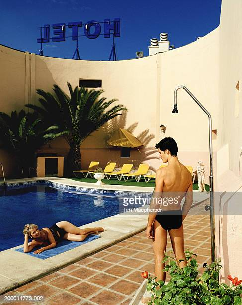 Young man and mature woman looking at each other beside hotel pool
