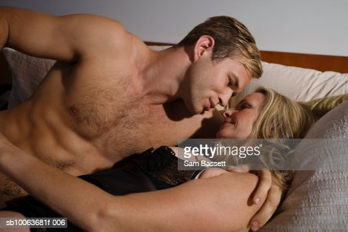 Young man and mature woman lying on sofa, smiling : Stock Photo