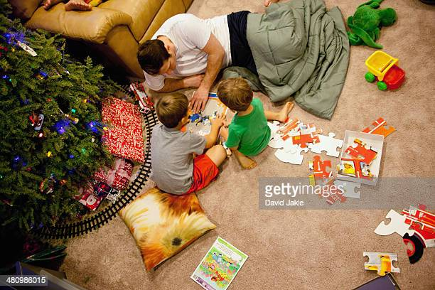 Young man and nephews playing with jigsaw puzzles on floor