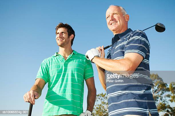 Young man and senior man holding golf clubs outdoors