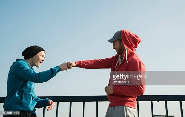 Young man and teenager at railing under blue sky