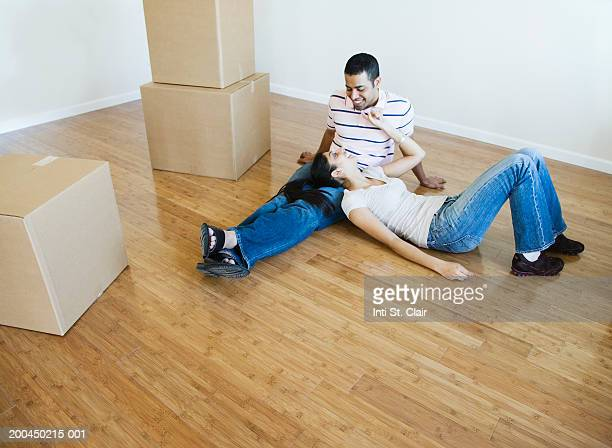 Young man and woman beside stacks of cardboard boxes in living room