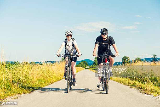 Young man and woman biking in nature