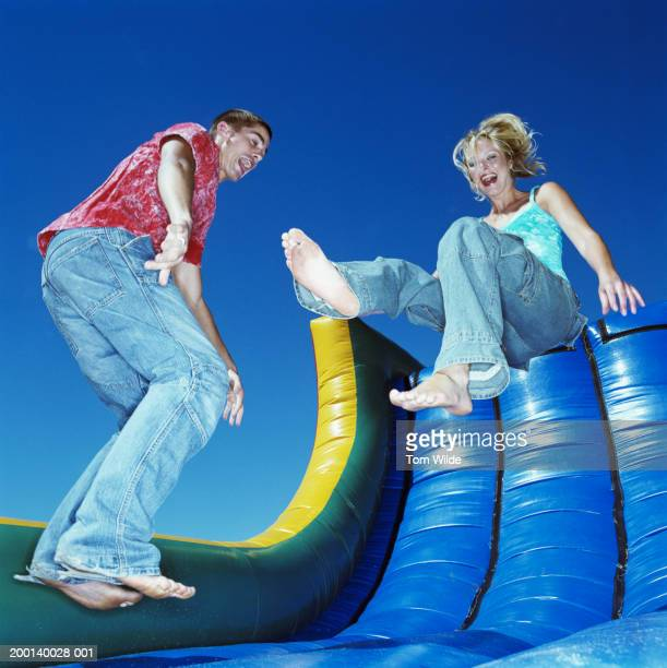 Young man and woman bouncing on inflatable slide, low angle view