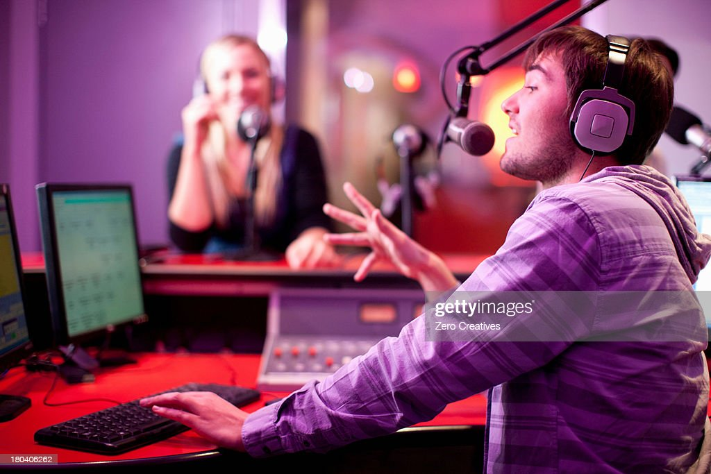 Young man and woman broadcasting in recording studio