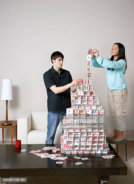 Young man and woman building house of cards on coffee table