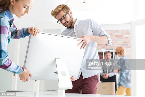 Young man and woman carrying computer screen in office