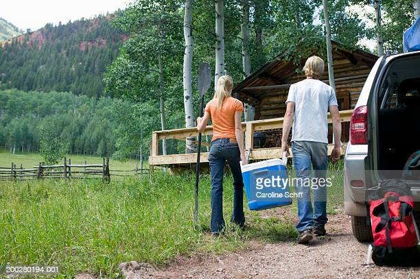 Young man and woman carrying cooler from SUV to log cabin, rear view