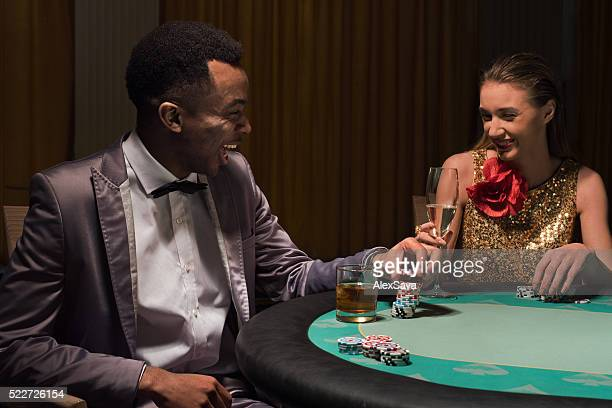 Young man and woman chatting at the poker table