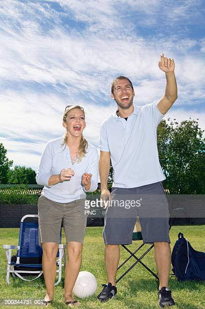 Young man and woman cheering on sidelines of soccer game