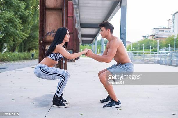 Young man and woman doing counterbalanced squat