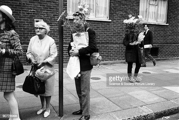 Young man and woman each holding a bouquet of flowers from Chelsea Flower Show standing in a bus stop queue 1968 Taken at Chelsea London Photographer...