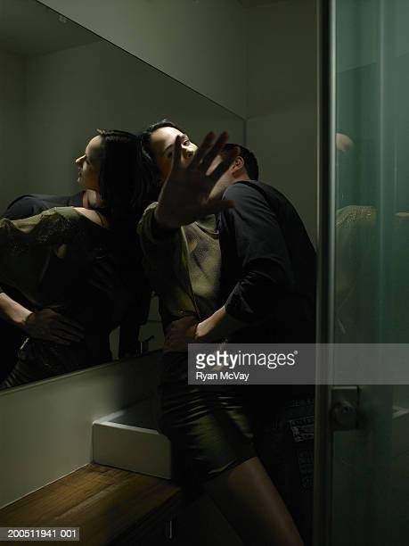 Young man and woman embracing in public restroom, side view