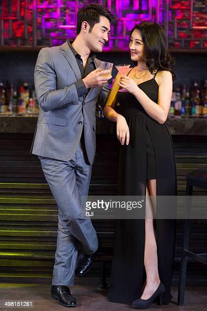 Young man and woman flirting at bar