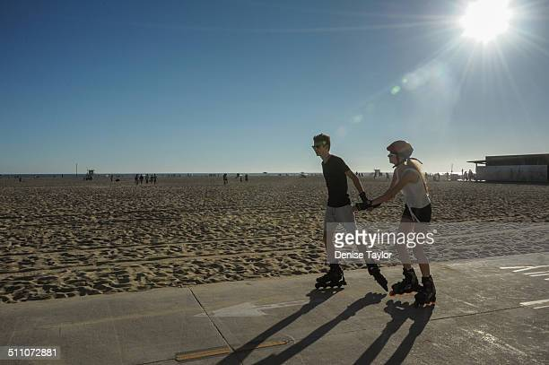 A young man and woman hold hands as they roller skate under the sun along the boardwalk on Santa Monica Beach August 172014