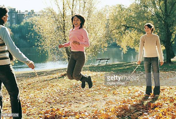 Young Man and Woman Holding a Skipping Rope in a Park and a Portrait of a Young Woman Skipping