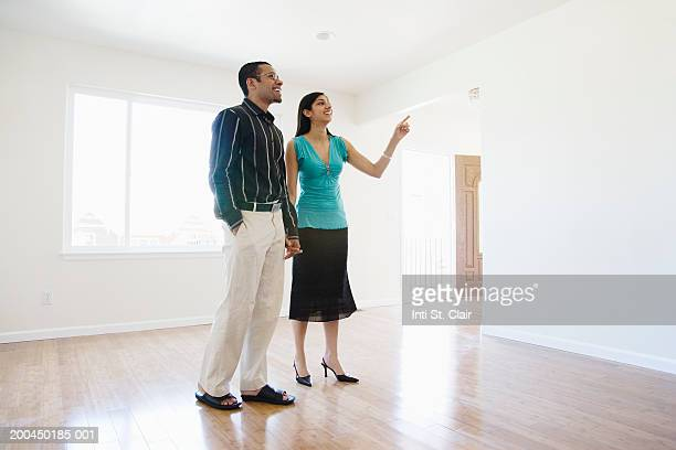 Young man and woman holding hands in empty living room, woman pointing