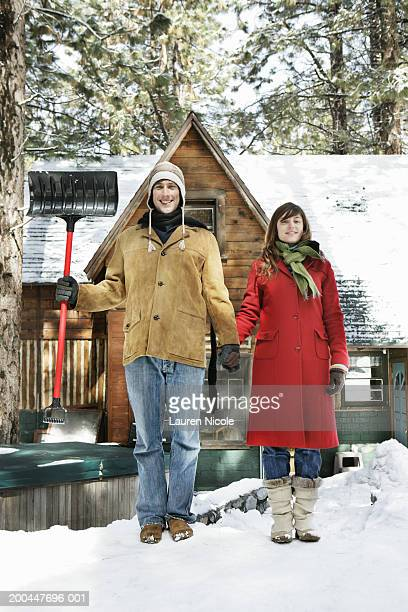 Young man and woman holding hands, standing in snow, man with shovel