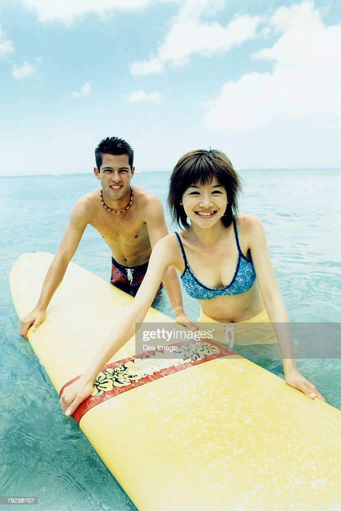 Young man and woman holding surfboard in water : Stock Photo