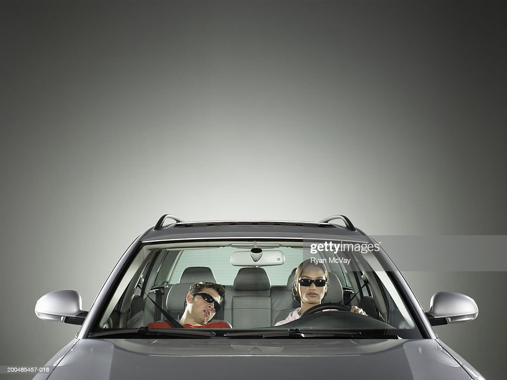 Young man and woman in car, woman driving while man sleeps : Stock Photo