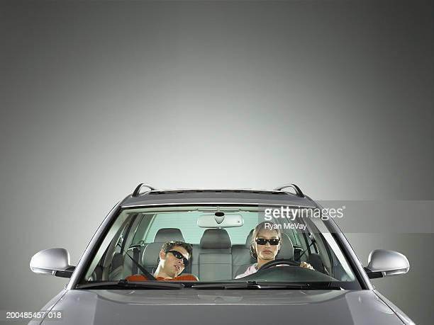 Young man and woman in car, woman driving while man sleeps