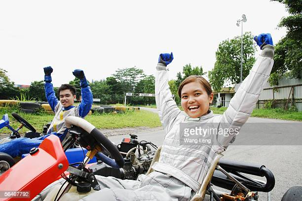 Young man and woman in go-carts, hands outstretched, smiling at camera
