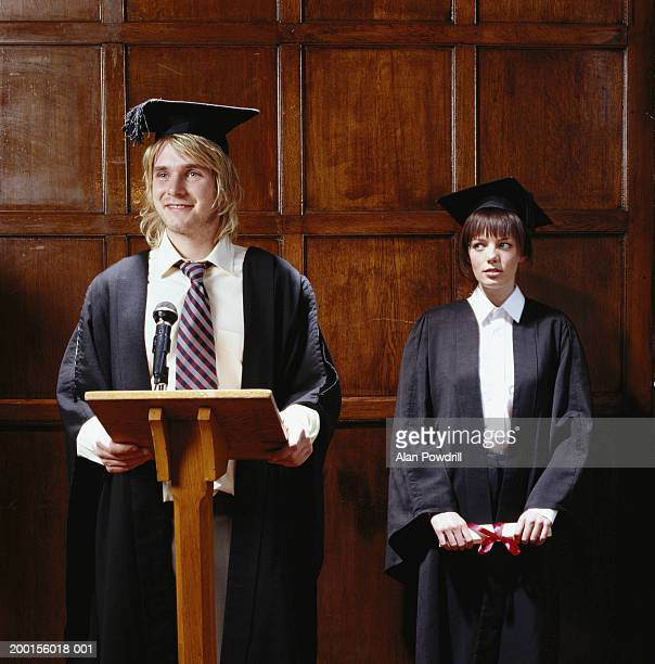 Young man and woman in graduation attire, young man standing at podium