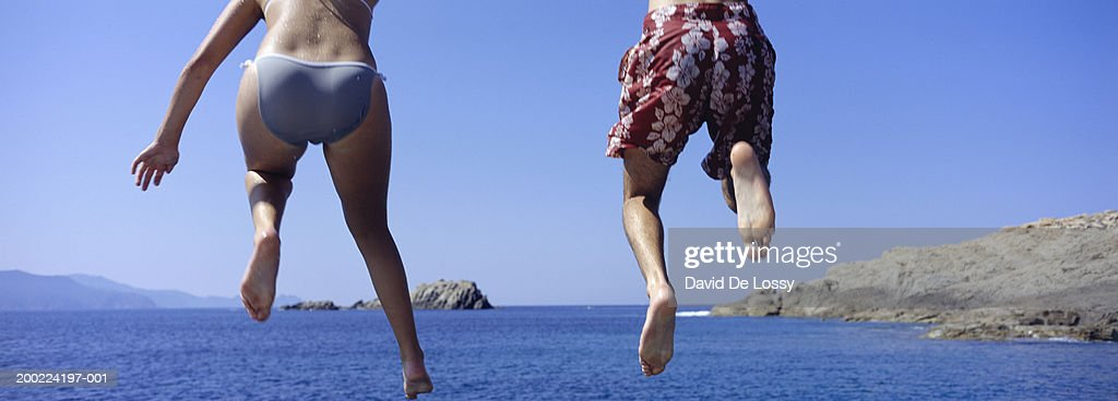 Young man and woman jumping into ocean, rear view
