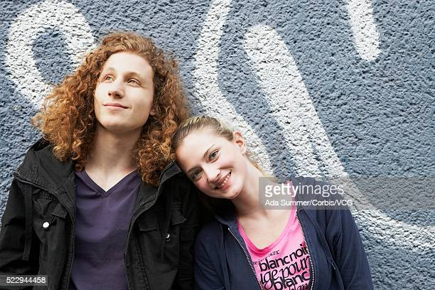 Young man and woman leaning against wall