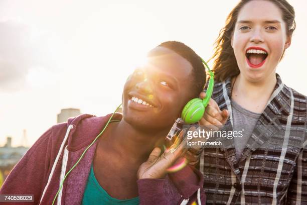 Young man and woman listening to headphone music at roof party in London, UK