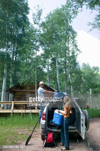 Young man and woman loading camping gear into SUV beside log cabin : Stock Photo