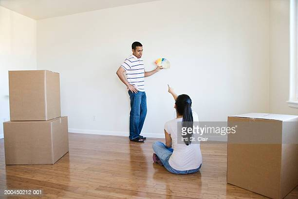 Young man and woman looking at paint samples in empty living room