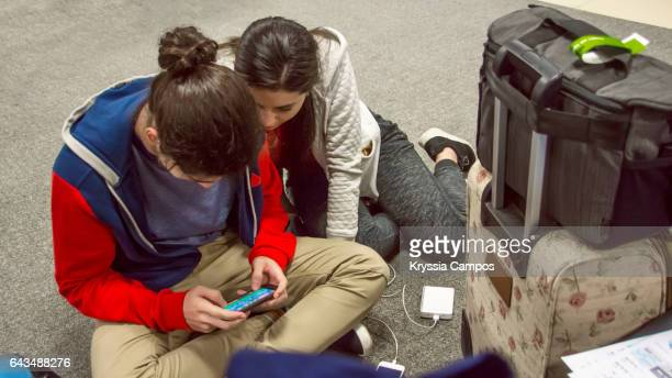 Young man and woman looking at smartphone at airport lounge