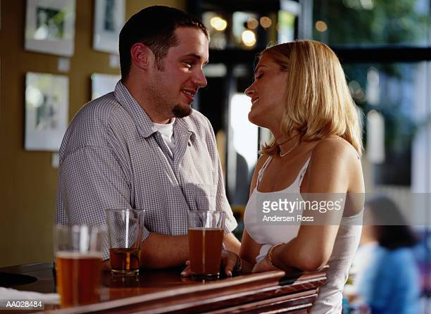 Young man and woman looking into each other's eyes, standing at bar