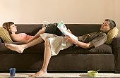 Young man and woman lying on sofa, reading magazines, side view
