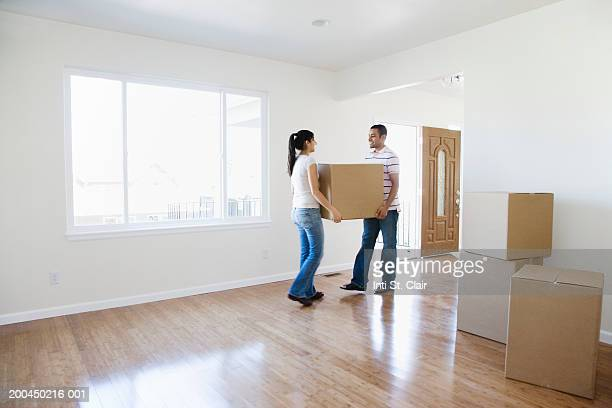 Young man and woman moving cardboard boxes into new home