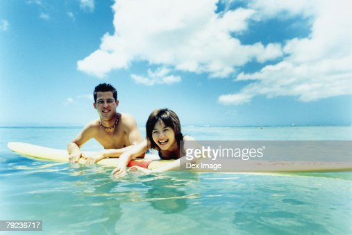 Young man and woman on surfboard in water : Stock Photo